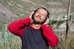 一个有胡子的人听到在耳机的音乐,本质上 有在它后的山 他是愉快的 免版税库存图片