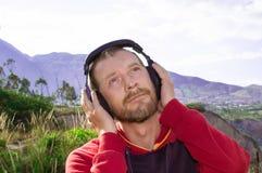 一个有胡子的人听到在耳机的音乐,本质上 库存图片