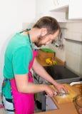 一个有胡子的人在厨房里烹调,切葱 免版税库存照片