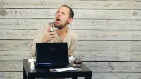一个有胡子的人工作在计算机和咳嗽 影视素材