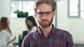 一个有胡子的人的画象玻璃的和一个偶然格子衬衫身分的在办公室中心在的大厅 股票录像