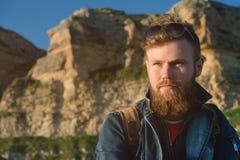 一个有胡子的时髦的旅客的特写镜头画象一个盖帽的反对史诗岩石 时刻旅行概念 免版税库存照片