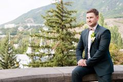 一个有胡子的更加熟悉内情的新郎的画象一套蓝色衣服的和在婚礼的一条红色领带走 库存图片