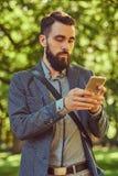 一个有胡子的男性的画象与时髦的理发的在便衣,在电话写一则消息,在公园站立 免版税库存图片