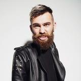 一个有胡子的年轻人的情感画象皮夹克的在演播室 免版税库存图片