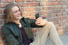 读一个有趣的正文消息的现代年轻人 隔绝在有拷贝空间的砖墙上 库存图片