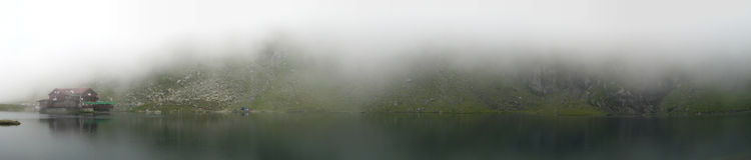一个有雾的山湖的之家 库存图片