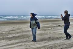 一个有风海滩的两个年轻人 免版税库存照片