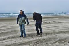 一个有风海滩的两个年轻人 库存照片