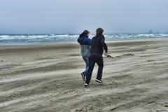一个有风海滩的两个年轻人 免版税库存图片