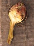 一个朝鲜蓟的一半在木头的 免版税库存图片