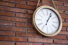 一个木壁钟的媒介近景有垂悬在红砖墙壁的罗马数字的 库存照片