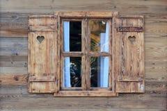 一个木小屋的窗口与心脏的在窗帘 免版税库存照片