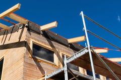 一个木屋顶的建筑在一个生态房子里 在大厦信封的外在工作 房子ne的木结构 免版税库存图片