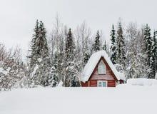 一个木房子在一个多雪的森林里 免版税库存照片