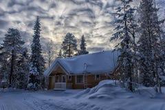 一个木房子在积雪的森林里在拉普兰地区 免版税库存图片