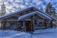 一个木房子在积雪的森林里在拉普兰地区 免版税图库摄影