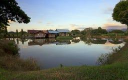 一个木房子的反射一个湖的在沙巴,婆罗洲的日落的 库存图片