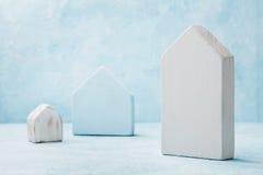 一个木房子的模型蓝色背景的 建筑房地产,保险得在家,修造,抵押和建筑概念 免版税库存照片