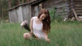 一个木房子的背景的女孩收集野花花束  股票录像