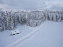 一个木房子空中在它后的雪盖的照片在森林旁边的和山在寒冷冬天 库存照片