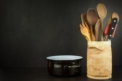 一个木架子的工具厨师 在一个陶瓷容器的厨房器物在黑背景 免版税库存图片