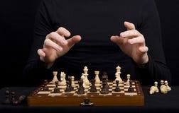 一个木棋盘的特写镜头有棋形象和手的  库存图片