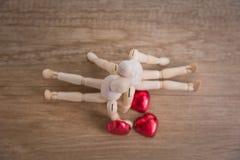 一个木玩偶人用心形的巧克力在情人节 免版税库存照片
