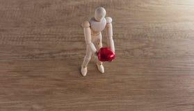 一个木玩偶人用心形的巧克力在情人节 库存照片