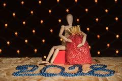 一个木玩偶木偶坐并且拿着与a的一个红色新年` s袋子 库存图片