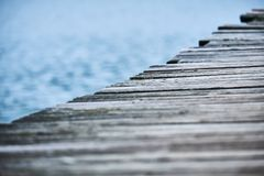 一个木码头的边的特写镜头运行对角地横跨与湖的框架的可看见在背景变异1 库存照片