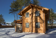 从一个木粱的冬天房子在反对蓝天的一个森林里 库存照片