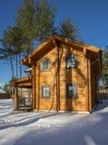 从一个木粱的冬天房子在反对蓝天的一个森林里 库存图片