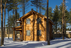 从一个木粱的冬天房子在反对蓝天的一个森林里 免版税库存照片
