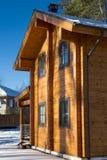从一个木粱的冬天房子在反对蓝天的一个森林里 免版税库存图片