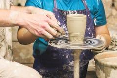 一个未加工的泥罐在陶瓷工的手上 瓦器的车间 免版税库存照片