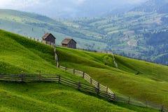 一个未加工的绿色草甸的风景有测深索的对谷仓,Bucovina,罗马尼亚 免版税图库摄影