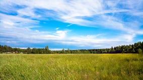 一个未开展的领域和晴朗的天空与云彩 农村的横向 免版税库存图片