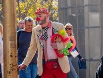 一个未认出的人加工好的小丑在缆车附近使人发笑 免版税库存图片