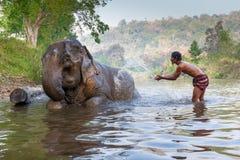 一个未认出的人在河显示使用与大象 免版税库存图片
