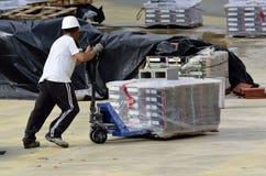 一个未认出的人,运载在现有量的一辆独轮车 库存图片