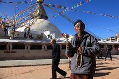 一个未认出的献身者提议祈祷在佛教朝圣中心Boudhanath Stupa 库存照片