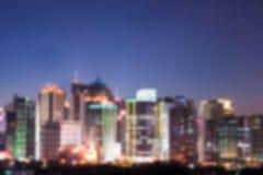 一个未认出的现代城市的地平线的被弄脏的背景在晚上 库存照片