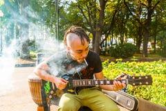 一个未认出的年轻人弹吉他并且抽在M的香烟 免版税图库摄影