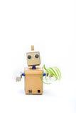 一个机器人在手上拿着绿色植物 垂直的照片 库存照片