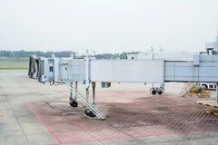 从一个机场终端门的喷气机桥梁在新加坡 免版税库存照片