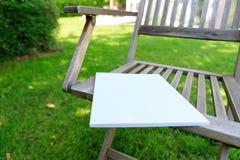 一个杂志封面的大模型在一把木椅子的在庭院里在su 免版税库存照片