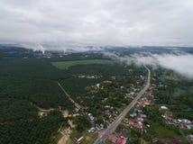 一个村庄的鸟瞰图在棕榈油种植园和工业区附近的 免版税图库摄影