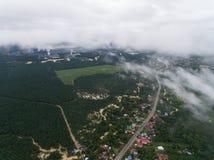 一个村庄的鸟瞰图在棕榈油种植园和工业区附近的 免版税库存照片