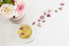 一个杯子与干玫瑰的健康清凉茶 在轻的大理石桌,顶视图上的美丽的鲜花 桃红色玫瑰和大丁草 库存图片